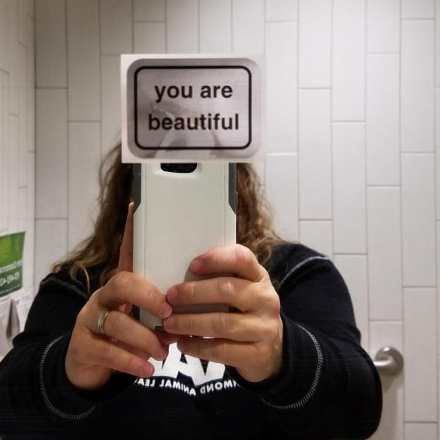 Sticker taped to mirror in Gender Neutral bathroom