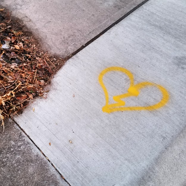 Broken heart spray painted in yellow on a sidewalk